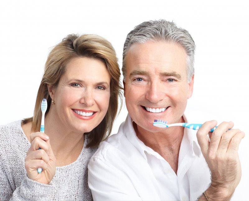 Older couple holding toothbrushes together and smiling